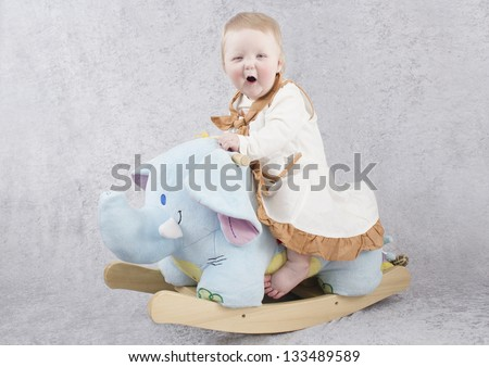 Baby on a rocking horse - stock photo