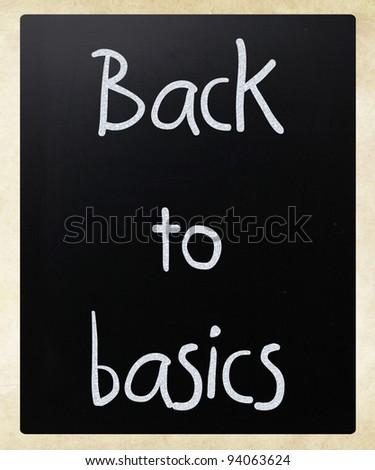 """Back to basics"" handwritten with white chalk on a blackboard - stock photo"