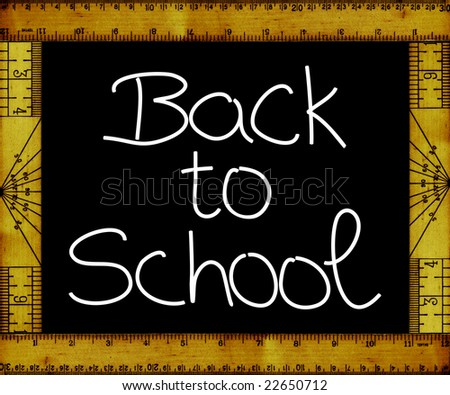 """Back to school"" hand-written on blackboard with frame made of vintage rulers"