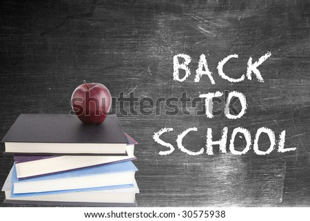 """Back to school"" written on blackboard in chalk with an apple on top of a pile of books"