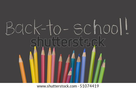 """""""back to school"""" written on chalkboard with multicolored pencil crayons - stock photo"""