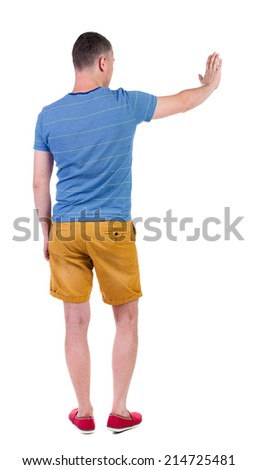 back view of man. Young man in shorts presses down on something. Isolated over white background. Rear view people collection. backside view of person. she holds his hand open, palm forward - stock photo