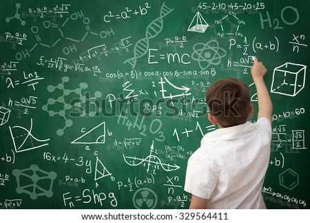 Back view of schoolboy writing math formula on green  blackboard - stock photo