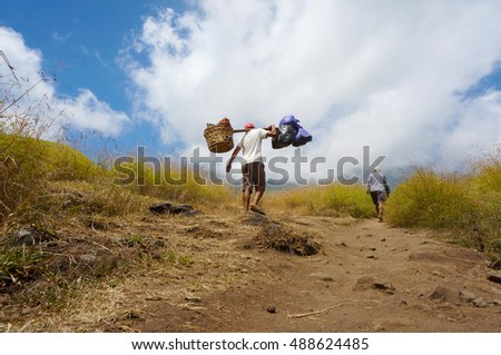 Back view Rinjani mount lombok Indonesia porter carry food necessities
