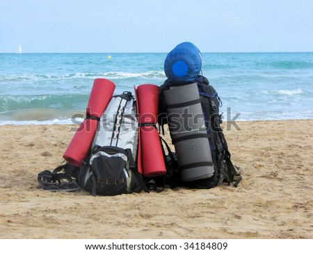 backpack and tourist equipment on a beach of Mediterranean sea, Spain, Barcelona