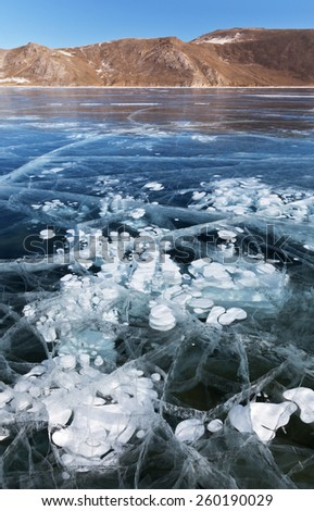 Baikal Lake in winter. White layered bubbles in transparent ice - stock photo