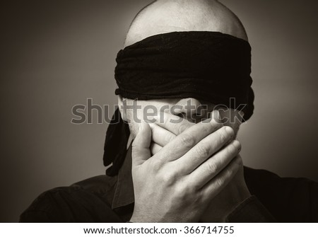 Bald man  blindfolded  and shut his mouth with his hands
