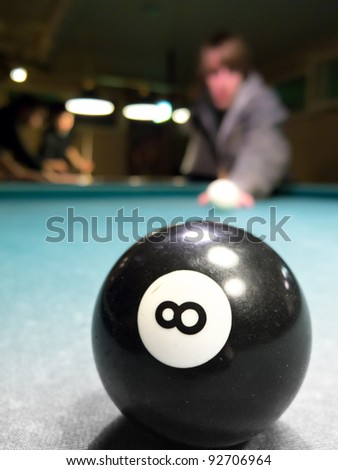 8-Ball and blurry person in background - stock photo