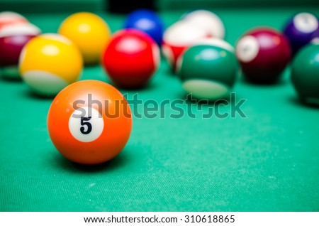 5 Ball from pool or billiards on a billiard table