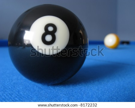 8 ball on a pool table with the 9 ball in the distance.