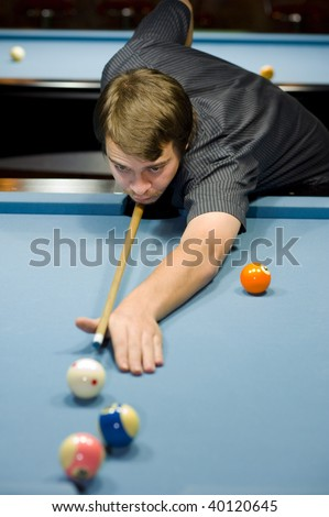 8 ball pool game: caucasian taking a shoot. focus on his face with a shallow depth of field - stock photo