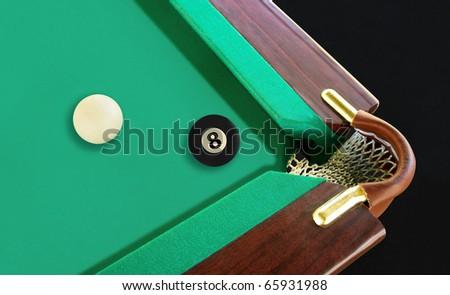 8 ball resting near the corner pocket - stock photo