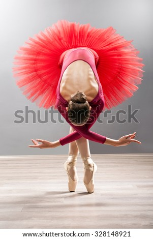 Ballerina is wearing a red tutu and pointe shoes - stock photo