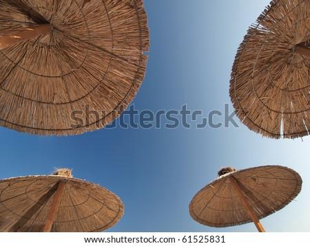 4 bamboo parasols on a beach - stock photo