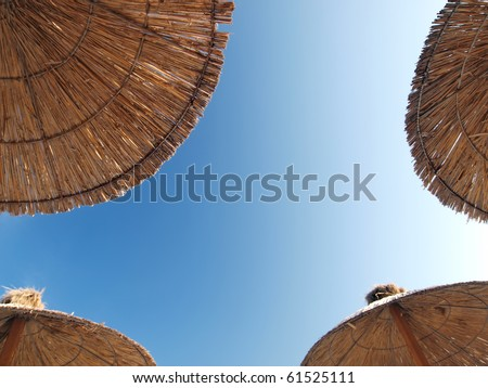 4 bamboo parasols with clear blue sky background - stock photo