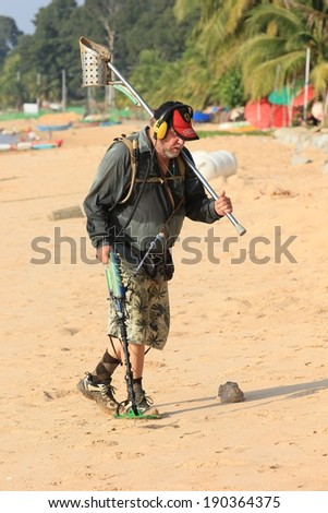 BANG SARAY BEACH, THAILAND - APRIL 24,2014 Old man looking for metal objects with a metal detector  on April 24,2014 in the Bang Saray beach Sattahip Chon Buri Thailand - stock photo