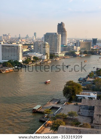 Bangkok with the river and boats at sunset. In the foreground is the river with boats. On the banks of the river are tall modern hotels. End of the day, faint twilight. Clear blue sky.