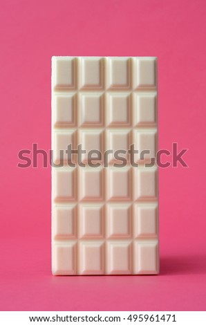 bar of white chocolate on pink background