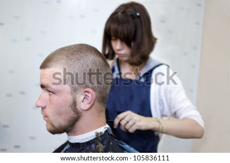 Barber cutting hair with clipper - stock photo