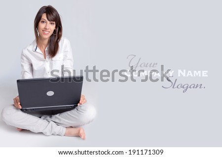 Barefoot young woman using her computer cross-legged on the floor  - stock photo