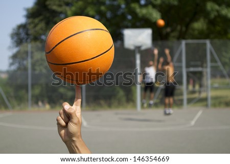 Basketball Spinning with blurred players in the background - stock photo