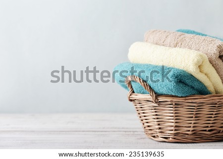Bath towels of different colors in wicker basket on light background - stock photo