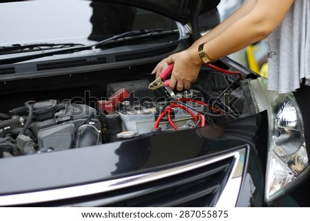 Battery charging cables connect to a car battery