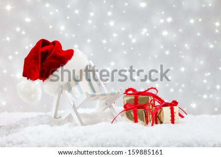 beach chair with santa hat and christmas gifts in snow before twinkled background