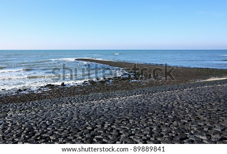Beach in Holland by the North Sea with black boulders and breakwater. - stock photo