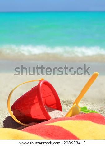 Beach toys and towel in red and yellow in  sand on a tropical Caribbean beach with blue ocean in the background       - stock photo