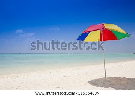 beach with a sunshade under a deep blue sky - stock photo