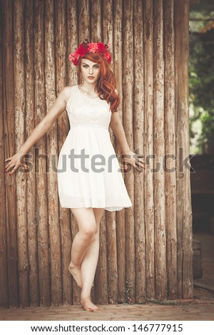 beautiful and sexy woman in village near  wooden wall - stock photo
