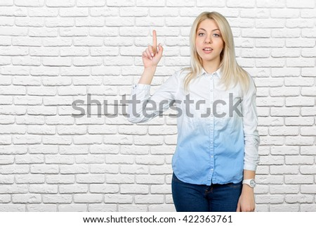beautiful blond business woman pointing at copy space - stock photo