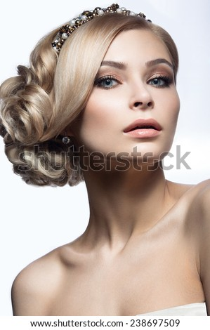 Beautiful blond girl in the image of a bride with a tiara in her hair. Picture taken in the studio on a white background. Beauty face. Wedding image. - stock photo