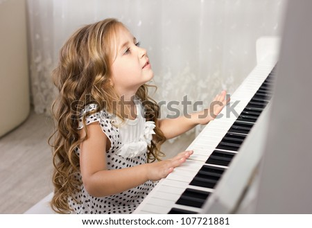 beautiful blond little girl playing near a piano in a white room - stock photo