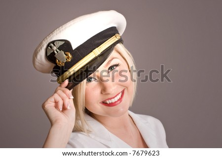 beautiful blond woman tipping generic officer's cap, room for copy - stock photo