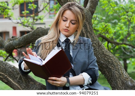Beautiful blonde reads the book - stock photo