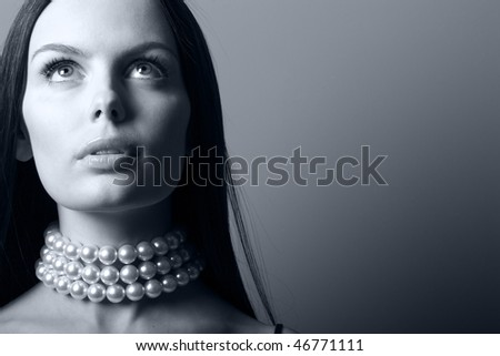 Beautiful brunette woman in pearl beads. Black and white photo. - stock photo