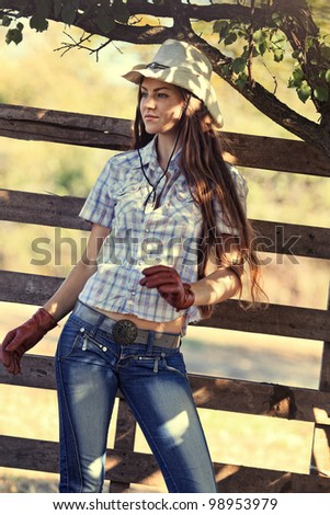 beautiful cowgirl in stetson next to wooden fence - stock photo