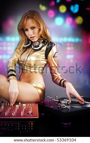 Beautiful DJ girl on decks on the party with the disco light on the background - stock photo