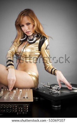 Beautiful DJ girl on decks on the party with the plain gray background - stock photo