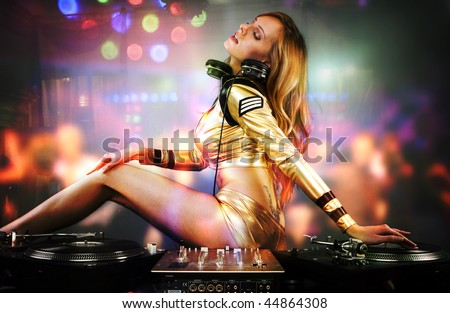 Beautiful DJ girl on decks playing on the party people on the dance floor - stock photo
