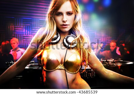 Beautiful DJ girl standing in the front of the decks - stock photo