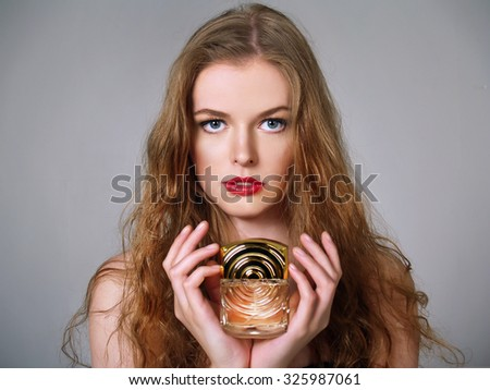 Beautiful European girl with long blonde hair holds perfumes