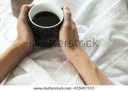 Beautiful female sitting on the bed in front of window relaxing and drinking coffee. Relaxing concept. - stock photo