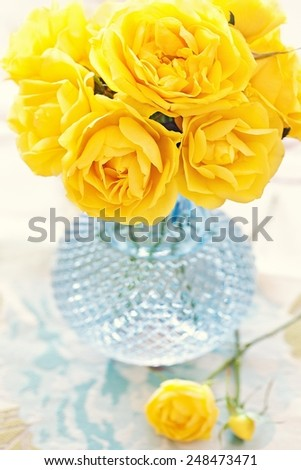 beautiful flowers. yellow roses in a blue vase on the table. - stock photo