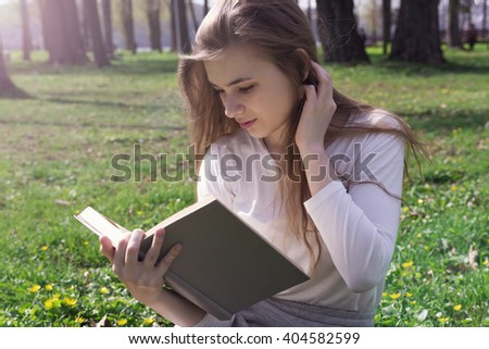 beautiful girl reading a book in the park