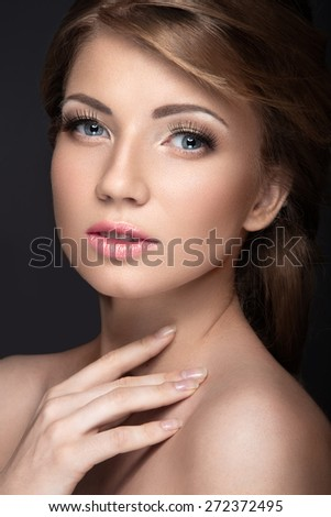 Beautiful girl with a gentle bridal makeup and long eyelashes. Beauty face. Picture taken in the studio on a black background. - stock photo