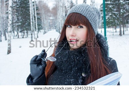 Beautiful girl with glasses and a folder in winter park - stock photo