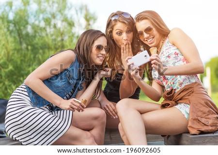 3 beautiful girlfriend watch the funny photos taken at  - stock photo